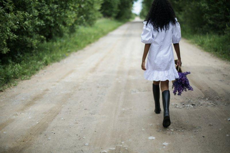 Frau im weißen Kleid mit Gummistiefeln auf einer Straße