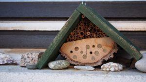 Ein kleines Insektenhotel mit grünem Dach.