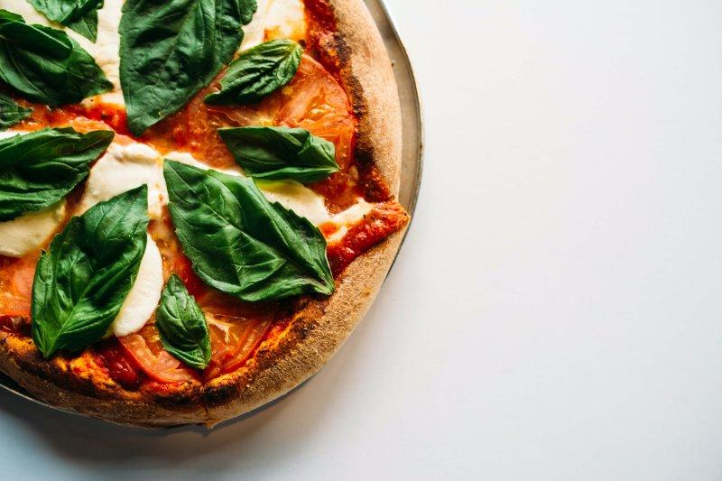 Fertige Pizza mit Basilikum auf einem Pizzastein