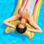 Frau schwimmt mit einer Luftmatratze auf dem Wasser ihres Aufstellpools.