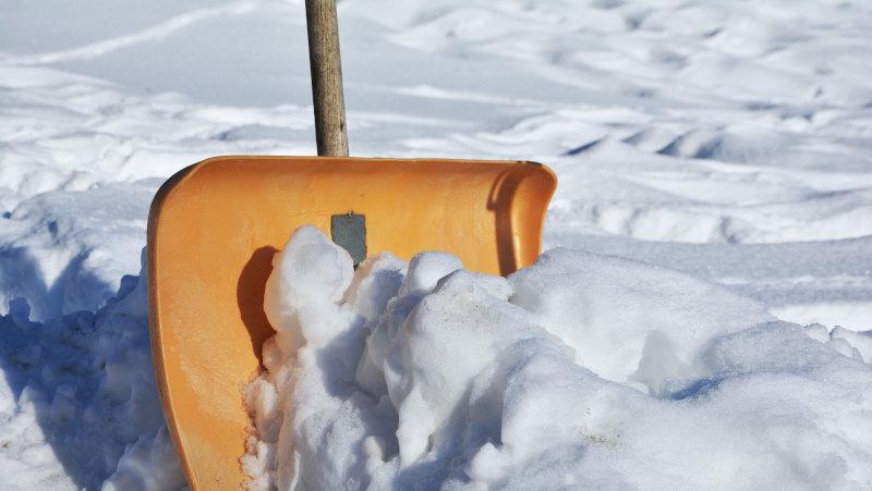 Schnee mit der Schneeschaufel schippen
