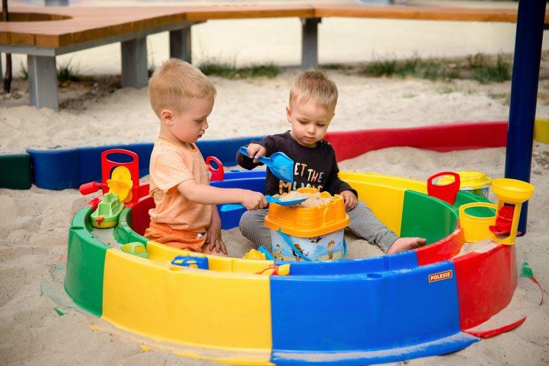 Kinder spielen mit Wasser und Sand