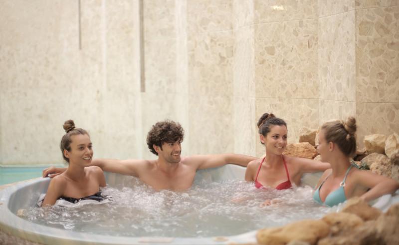 4 erwachsene Personen sitzen zusammen in einem Whirlpool.
