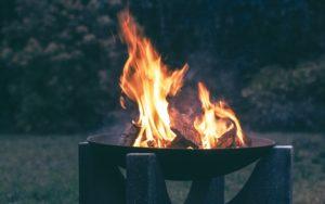 Schwarze Feuerschale mit lodernden Flammen im Freien