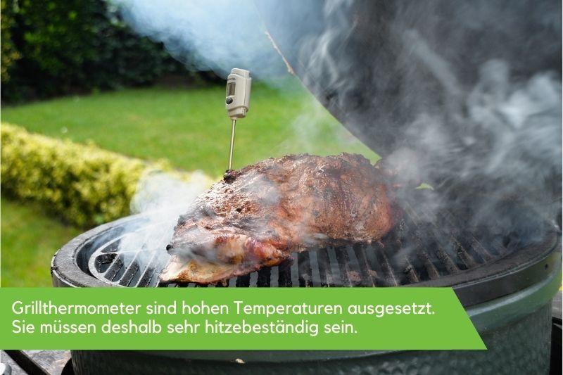 Grillthermometer in einem Stück Fleisch, welches auf einem rauchenden Grill liegt