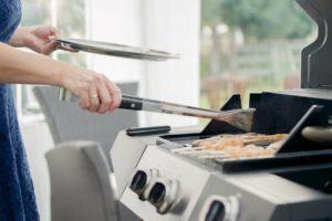 Eine Frau grillt an einem Gasgrill