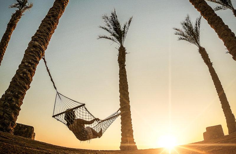 Frau liegt bei Sonnenuntergang in einer Hängematte unter Palmen