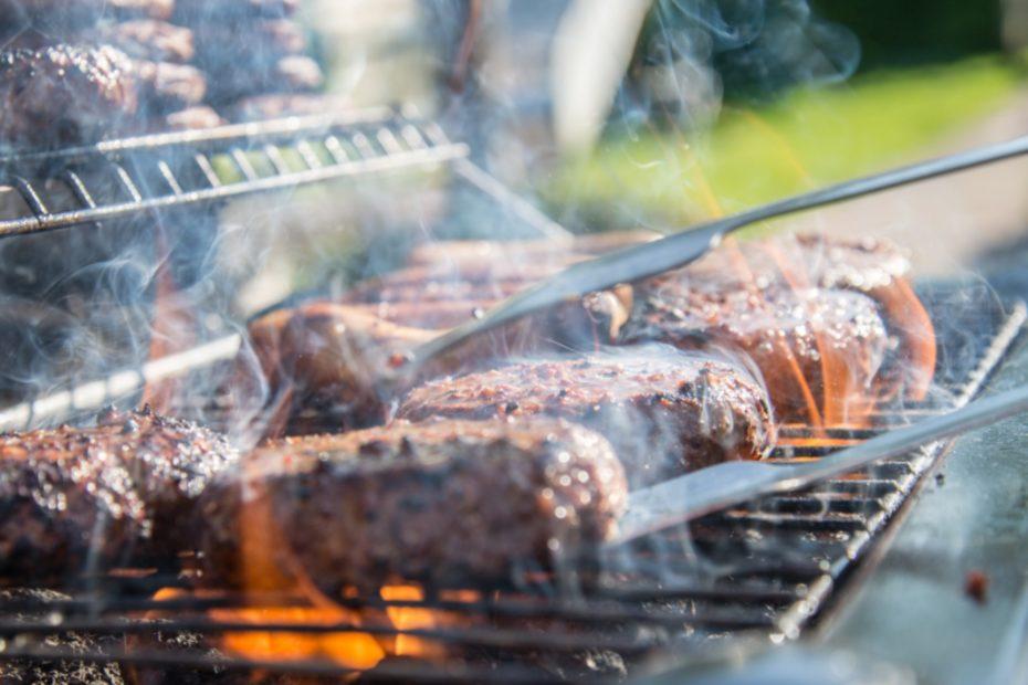 Brennender Grill mit mehreren Steaks