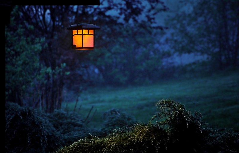 Gartenlampe hängt draußen in der Abenddämmerung