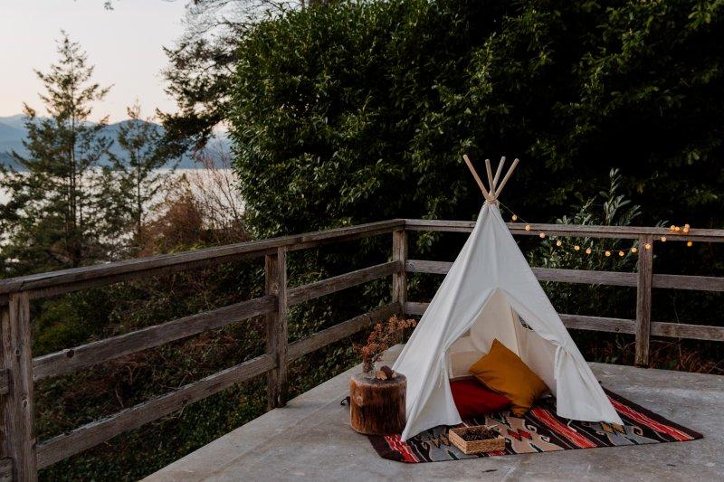 Ein Outdoor Teppich auf einer Terrasse unter einem Indianerzelt