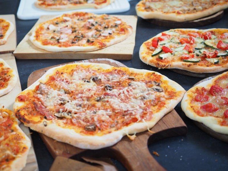 Mehrere Pizzen auf Pizzasteinen und eine Pizza auf einem Pizzaschieber