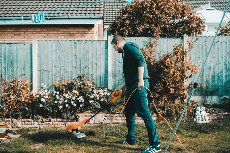 Mann der einen Rasenkantenschneider verwendet