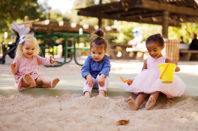 Drei Kinder, die im Sandkasten spielen