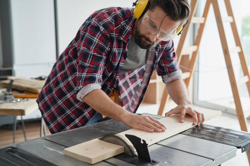 Mann sägt an einer Tischkreissäge