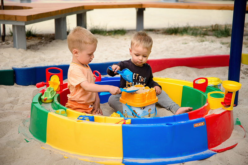 Ein Kunststoffsandkasten mit zwei Kindern darin