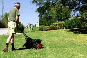 Mann beim Düngen seiner Rasenfläche