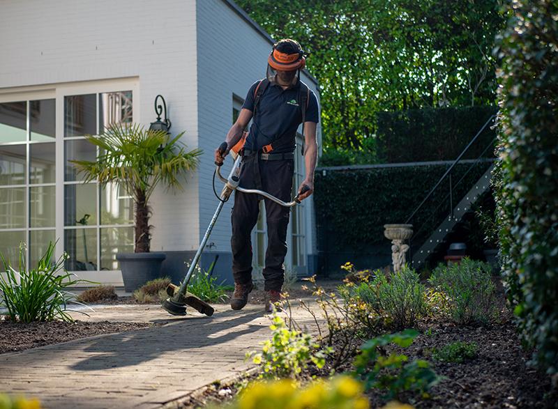 Mann mit Freischneider und Schutzkleidung im Garten