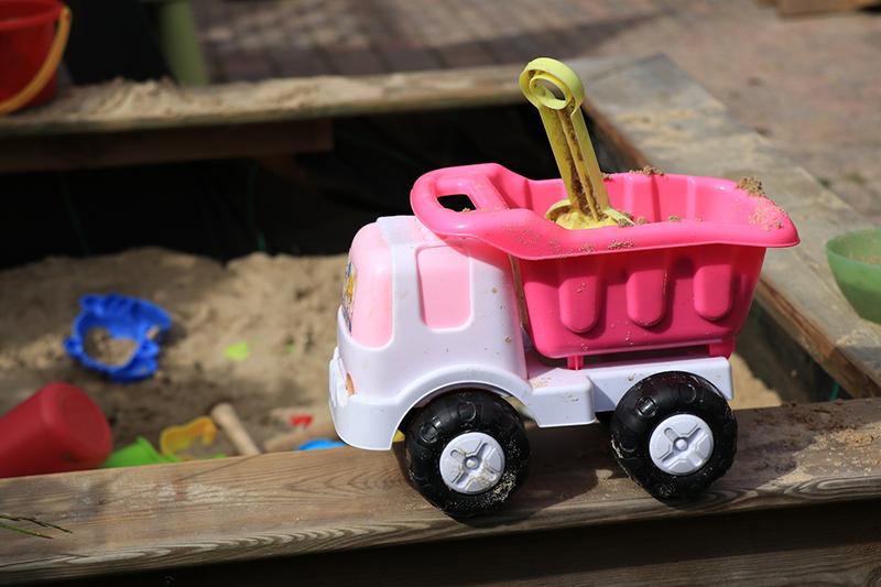 Ein Plastik LWK steht auf einem Holzsandkasten