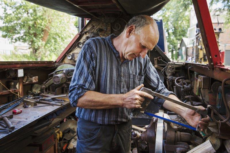 Mann sägt mit Bügelsäge