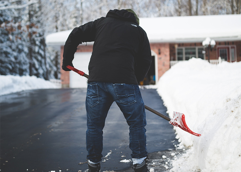 ein Mann schaufelt Schnee