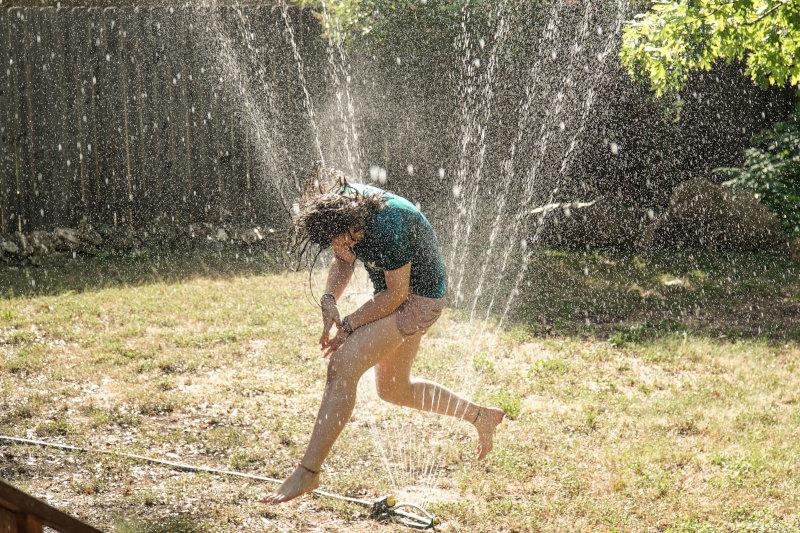 Kind springt durch den Wasserstrahl eines Viereckregners