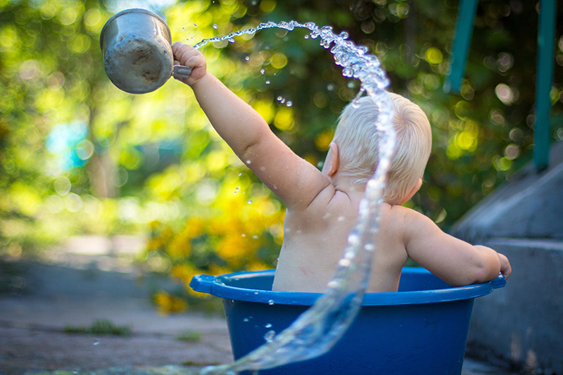 Kleines spielt Kind im Wassereimer