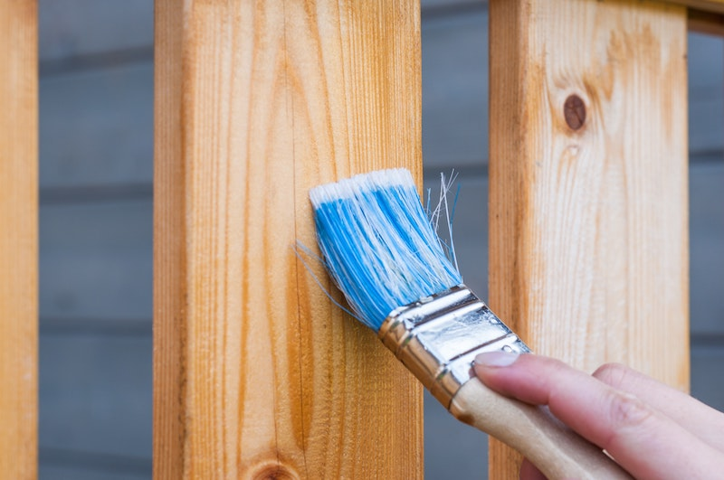 Eine Hand streicht einen Holzzaun mit einem Pinsel