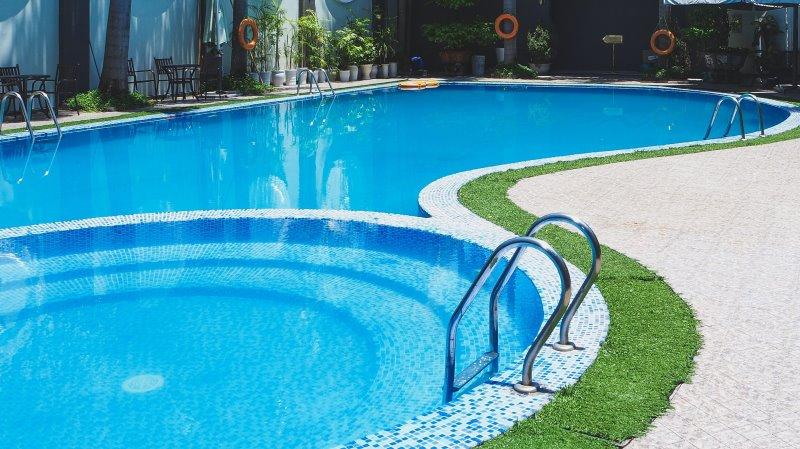 Ein großer Pool mit zwei Poolleitern aus Edelstahl