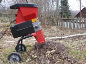 Ein roter Gartenhäcksler steht im Garten