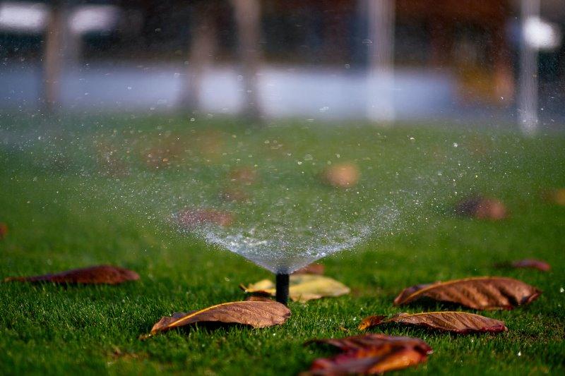Ein Versenkregner beregnet den Rasen im Herbst