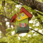 Ein buntes Vogelhäuschen an einem Baum.